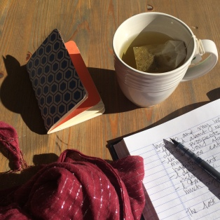 Cup of tea, scarf, notebook and journal on the deck at a beach retreat